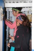 Auria empile les boîtes de conserve sur les étagères tandis que Pauline donne les consignes.